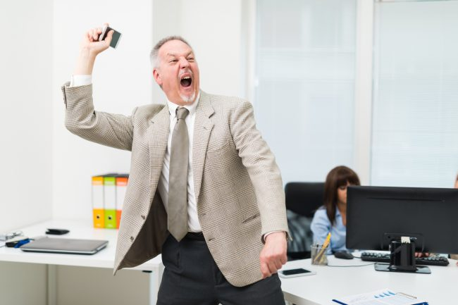 Angry businessman throwing away his phone