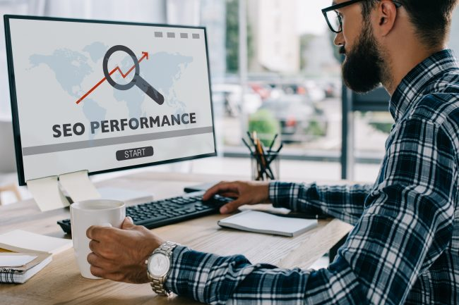 Young successful developer working with computer with SEO performance on screen at workplace