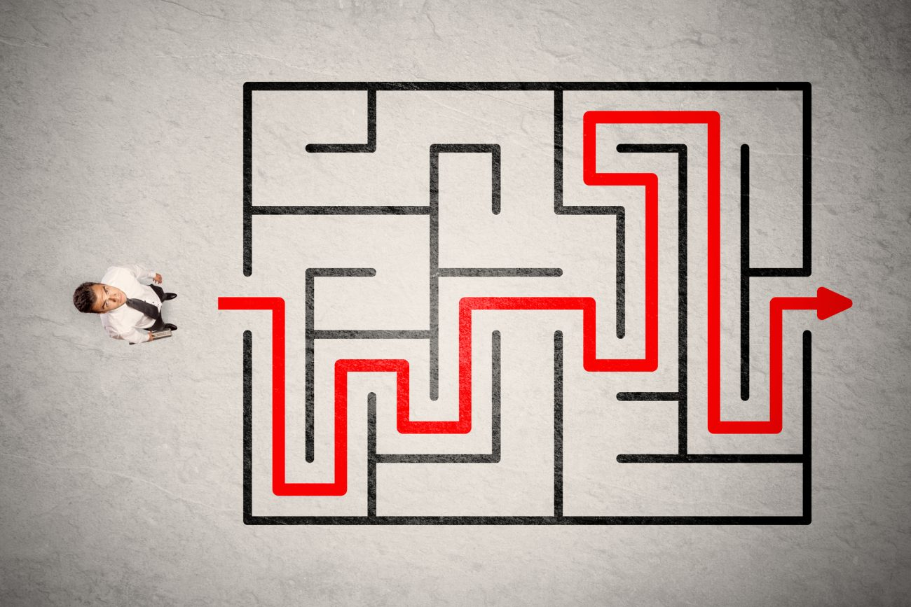 pencil-and-coffee-lost-businessman-found-the-way-in-maze-with-red-arrow