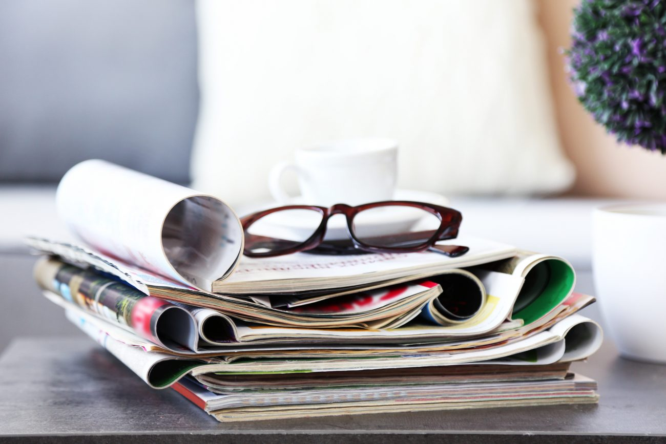 pencil-and-coffee-magazines-on-table-in-living-room-close-up