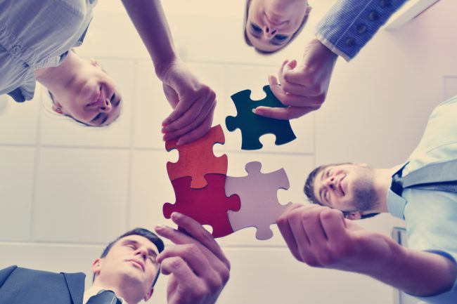 pencil-and-coffee-group-of-business-people-assembling-jigsaw-puzzle-and-represent-team-support-and-help-concept